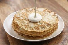 Śmietanka nalewa na świeżo robić blinis lub krepach, prosty słodki jedzenie obrazy stock