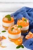 Śmietankowy panny cotta z pomarańcze galaretą w pięknych szkłach, świeża dojrzała mandarynka, błękitna tkanina na białym drewnian fotografia royalty free