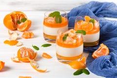 Śmietankowy panny cotta z pomarańcze galaretą w pięknych szkłach, świeża dojrzała mandarynka, błękitna tkanina na białym drewnian obraz royalty free