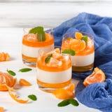 Śmietankowy panny cotta z pomarańcze galaretą w pięknych szkłach, świeża dojrzała mandarynka, błękitna tkanina na białym drewnian obraz stock