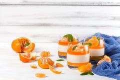 Śmietankowy panny cotta z pomarańcze galaretą w pięknych szkłach, świeża dojrzała mandarynka, błękitna tkanina na białym drewnian fotografia stock
