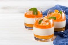 Śmietankowy panny cotta z pomarańcze galaretą w pięknych szkłach, świeża dojrzała mandarynka, błękitna tkanina na białym drewnian zdjęcia royalty free