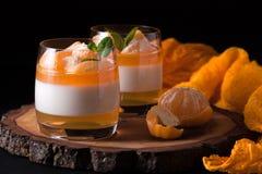 Śmietankowy panny cotta z pomarańcze galaretą w pięknych szkłach, świeża dojrzała mandarynka na drewnianej sekci na czarnym tle W zdjęcie stock