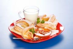 Śniadanie: dwa brzoskwini torty, mleko i dżemu na talerzu, Zdjęcia Royalty Free