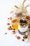 Śniadanie - granola, jogurt, jagody, dokrętki, miód, banatka Zdjęcie Royalty Free