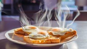 Śniadanie, Kłusujący jajka na Wznoszącym toast chlebie Zdjęcia Royalty Free