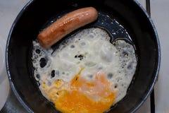 Śniadanie na niecce Smażący jajka z kiełbasianymi i zielonymi cebulami Zdjęcie Stock