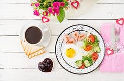 Śniadanie na walentynki ` s dniu - smażący jajko w formie serca, grzanek, kiełbasianych i świeżych warzyw, Obrazy Royalty Free