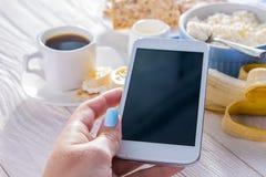 Śniadanie podczas gdy używać smartphone Fotografia Royalty Free