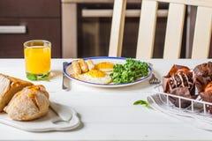 Śniadanie słuzyć z smażącymi jajkami, sałatką, słodka bułeczka i pomarańcze juic, obraz royalty free