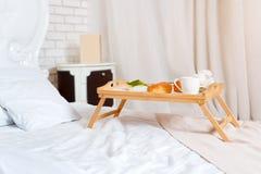 Śniadanie w łóżku, taca kawa, croissants i kwiaty, honeymoon Królewiątka wielkościowy łóżko w loft mieszkaniu Wczesny poranek prz obrazy stock