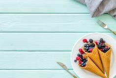 Śniadanie z świeżymi jagodami w gofrze konusuje i tableware na słuzyć mennicy zieleni drewniany stołowy tło odgórnego widoku mock obraz royalty free