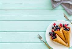 Śniadanie z świeżymi jagodami w gofrze konusuje i tableware na słuzyć mennicy zieleni drewniany stołowy tło odgórnego widoku mock obrazy royalty free