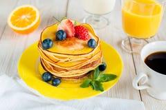 Śniadanie z blinami na koloru żółtego talerzu Obrazy Stock