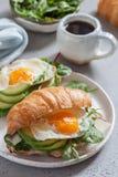 Śniadanie z Croissant ściska z jajkiem, sałatka liśćmi i avocado Smażącymi, Obrazy Royalty Free