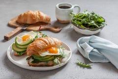 Śniadanie z Croissant ściska z jajkiem, sałatka liśćmi i avocado Smażącymi, Obraz Royalty Free