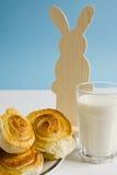 Śniadanie z cynamonowymi babeczkami i szkłem mleko na błękitnym tle z dekoracja Wielkanocnym królikiem Zdjęcie Stock