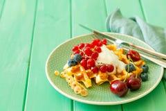 Śniadanie z goframi, wipped śmietanką, jagodami i granola, zdjęcie stock