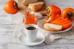 Śniadanie z persimmon owocowym dżemem kawą na drewnianym stole i obrazy stock