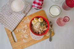 Śniadaniowa oatmeal owsianka z bananami, ziarnami, dokrętkami i mlekiem, Zdjęcie Royalty Free