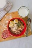 Śniadaniowa oatmeal owsianka z bananami, ziarnami, dokrętkami i mlekiem, Zdjęcia Royalty Free