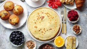 Śniadaniowego stołu położenie z świeżymi owoc, bliny, kawa, croissants zbiory wideo