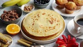 Śniadaniowego stołu położenie z świeżymi owoc, bliny, kawa, croissants zbiory