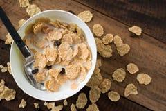 Śniadaniowego zboża cornflakes z mlekiem w pucharze na drewnianym stołowym tle Obrazy Royalty Free