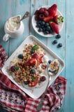Śniadaniowy granola jogurt, truskawka, czarne jagody, malinki na białym talerzu obrazy stock