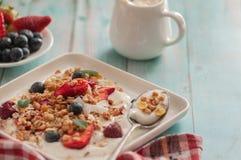 Śniadaniowy granola jogurt, truskawka, czarne jagody, malinki na białym talerzu zdjęcia royalty free