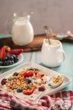 Śniadaniowy granola jogurt, truskawka, czarne jagody, malinki na białym talerzu zdjęcie stock