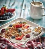 Śniadaniowy granola jogurt, truskawka, czarne jagody, malinki na białym talerzu zdjęcia stock
