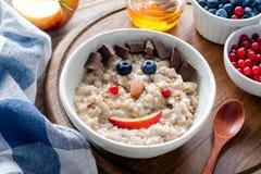 Śniadaniowy posiłek dla dzieciaków Oatmeal owsianka z śmieszną twarzą Zdjęcie Stock