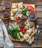 Śniadaniowy posiłek rozmaitości mieszkanie nieatutowy Odgórny widok na bufet drewnianej desce z mięsem, jajkami, warzywami, chleb fotografia royalty free
