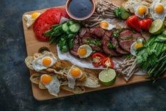 Śniadaniowy posiłek rozmaitości mieszkanie nieatutowy Odgórny widok na bufet drewnianej desce z mięsem, jajkami, warzywami, chleb obrazy royalty free