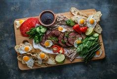 Śniadaniowy posiłek rozmaitości mieszkanie nieatutowy Odgórny widok na bufet drewnianej desce z mięsem, jajkami, warzywami, chleb obraz stock