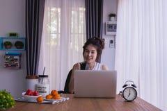 Śniadaniowy stół z młodą azjatykcią kobiety dink kawą, kobieta pracująca w ranku Smiley twarz fotografia stock