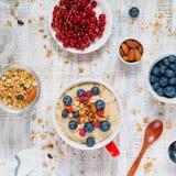 Śniadaniowy stół z owsianką, jagodami, muesli i migdałami oatmeal, obraz royalty free