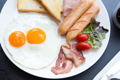 Śniadaniowy ustawiający na stole z hotdogs i bekonem, jajka na czerni Zdjęcie Royalty Free
