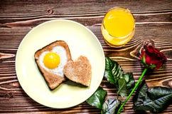 Śniadaniowy walentynki ` s dzień Na talerzu jest grzanka z smażącymi jajkami wśrodku serca Następnie na talerzu jest troszkę grza Zdjęcia Royalty Free