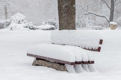 Śnieżna ławka w parku pod spada śniegiem fotografia royalty free