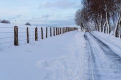 Śnieżna droga przez zima krajobrazu, drutu kolczastego ogrodzenie wzdłuż drogi zdjęcia royalty free