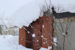 Śnieżna fala na dachu tworzącym silnymi wiatrami jako śnieg garaż spadał zdjęcia stock