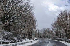 śnieżna halna droga rozjaśniająca z samochodem Obrazy Royalty Free