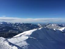 Śnieżna halna panorama i niebieskie niebo Fotografia Stock