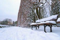 Śnieżna parkowa sceneria z empy ławką Fotografia Stock