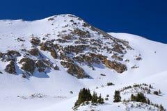 Śnieżna skalista góra w zimie z niebieskim niebem i skałą fotografia stock