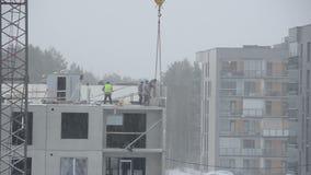 Śnieżni spadku i budowy pracownicy budują dom w zimie zbiory