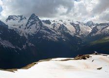 Śnieżni szczyty Dombai góry w opóźnionej wiośnie Fotografia Stock