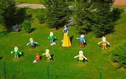 Śnieżny biały i siedem przyćmiewamy na zielonej trawie przy jawnym parkiem mnie zdjęcia royalty free